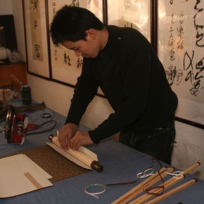Adhesive is added to the roller and it is placed in the body of the wall scroll.