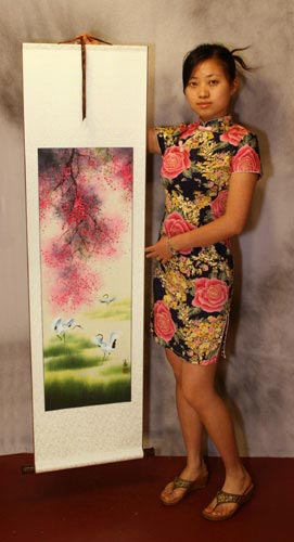 Yang Chen holds a four seasons cranes landscape wall scroll